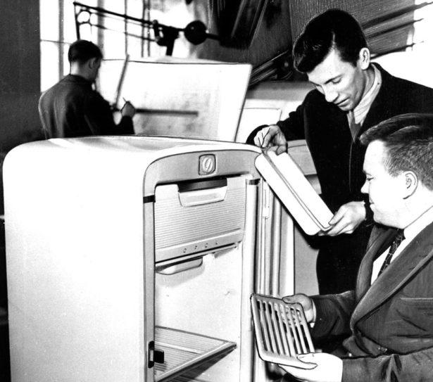 """Конструкторы П.И. Илюхин и В.П. Кучурин осматривают только что выпущенный на Орском механическом заводе холодильник """"Орск ХК-0100"""". 1960 г. Автор:Б. Клипиницер."""